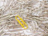 Yellow paper clip stand different from the crowd