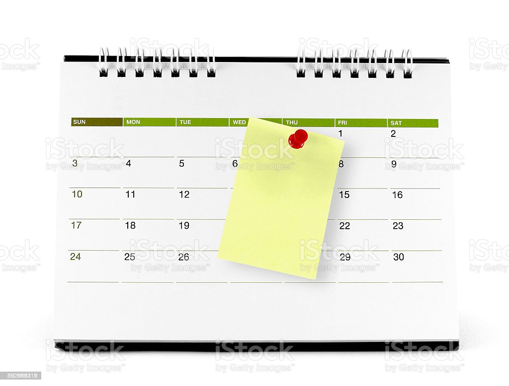 yellow paper note with red thumbtack on the calendar page stock photo