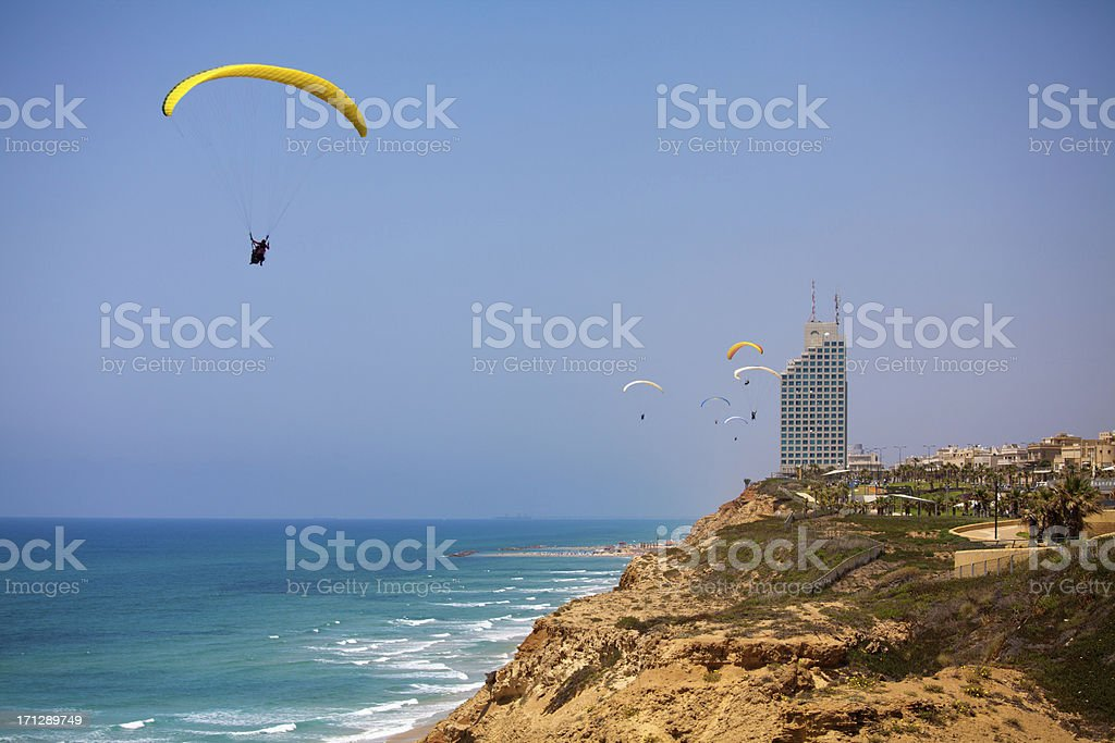 Yellow paraglader flying above Mediterranean Sea in Netanya, Isr stock photo