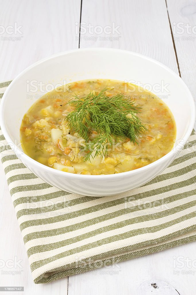 Yellow pea soup in bowl on white wooden background stock photo
