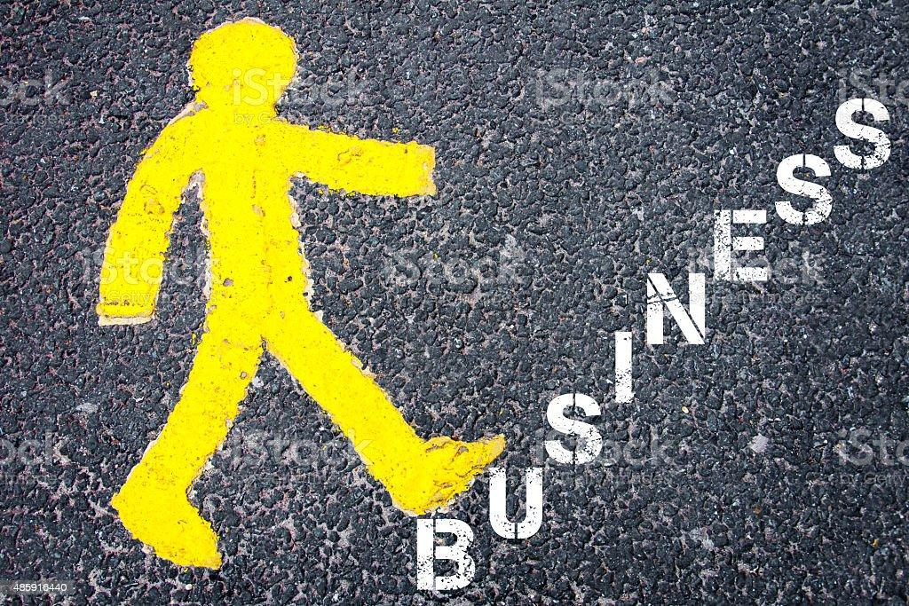 Yellow pedestrian figure walking towards BUSINESS stock photo