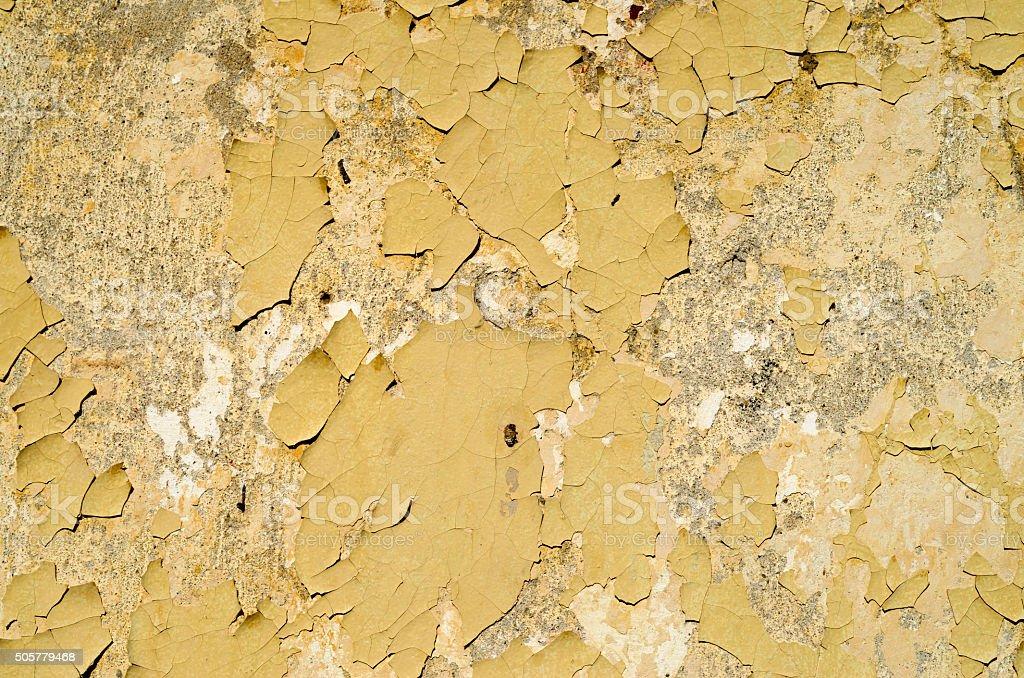 Yellow peeling paint on wall closeup stock photo