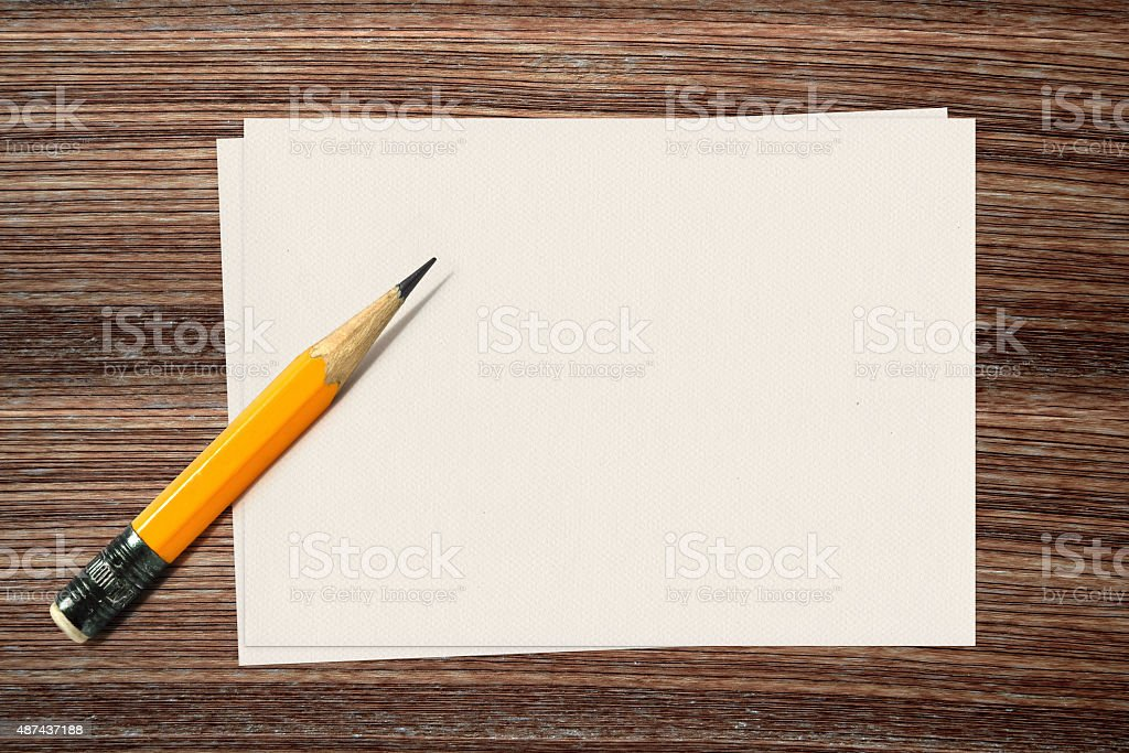 Yellow pencil and paper on wood background stock photo