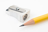 Yellow pencil tip and sharpener on white background