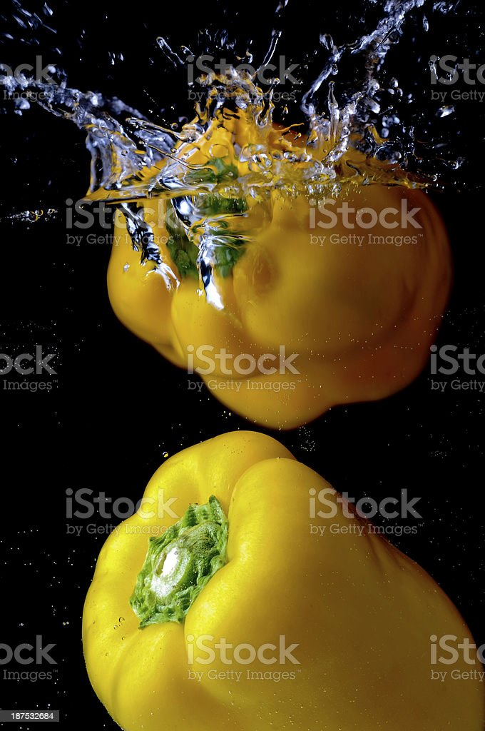 yellow peppers falling into water royalty-free stock photo