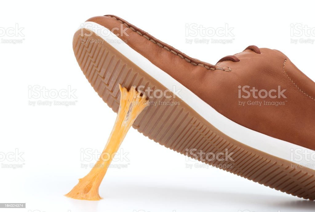 Yellow piece of gum stuck on bottom of brown shoe stock photo