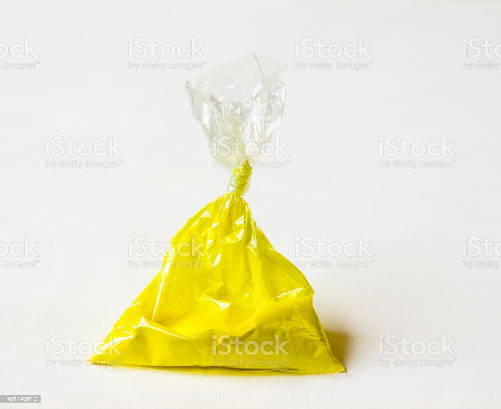 Yellow pigment in a plastic bag stock photo
