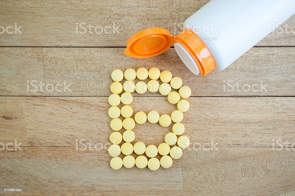 Yellow pills forming shape to B alphabet on wood background stock photo