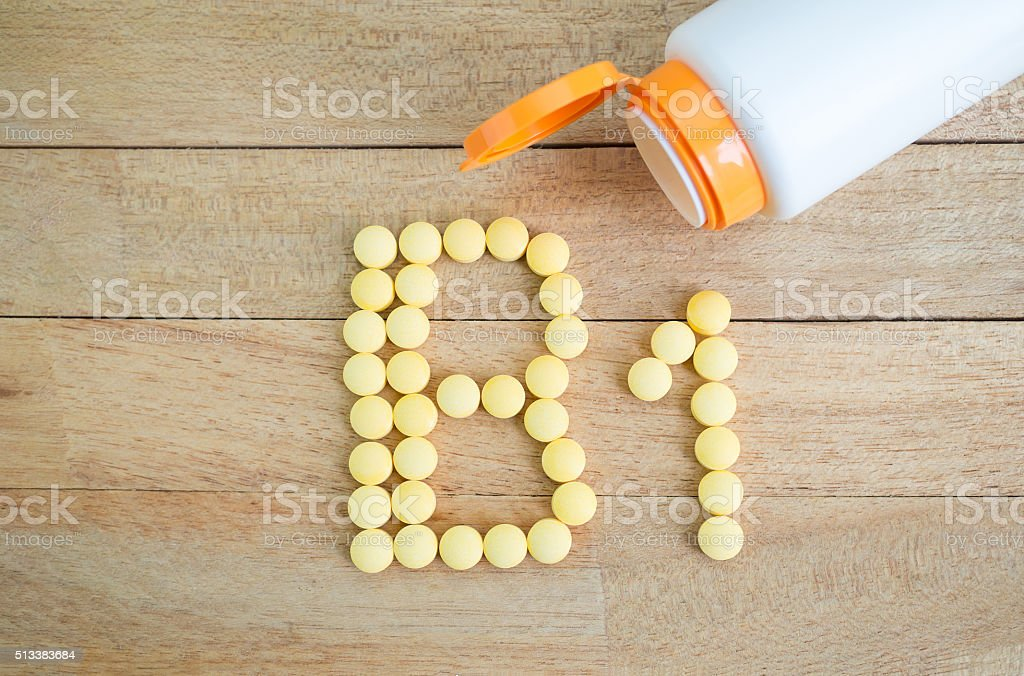 Yellow pills forming shape to B1 alphabet on wood background stock photo