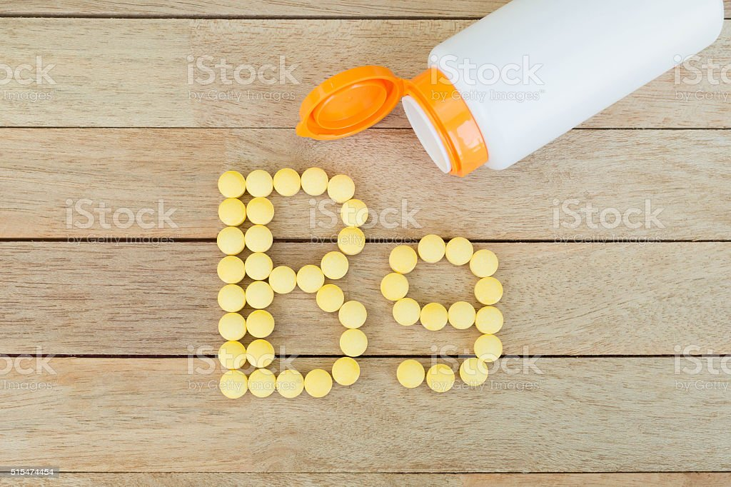 Yellow pills forming shape to B9 alphabet on wood background stock photo