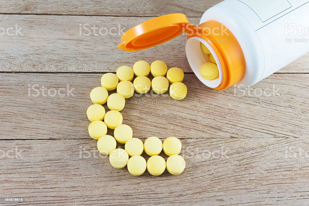 Yellow pills forming shape to C alphabet on wood background stock photo