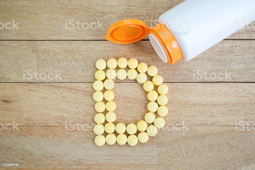 Yellow pills forming shape to D alphabet on wood background stock photo