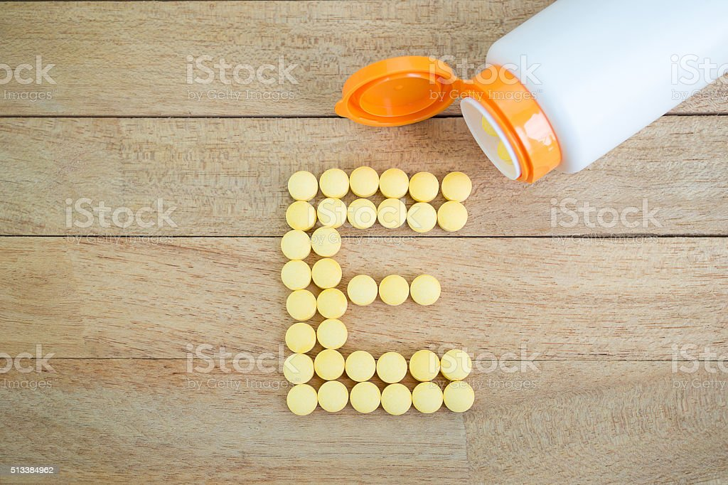 Yellow pills forming shape to E alphabet on wood background stock photo