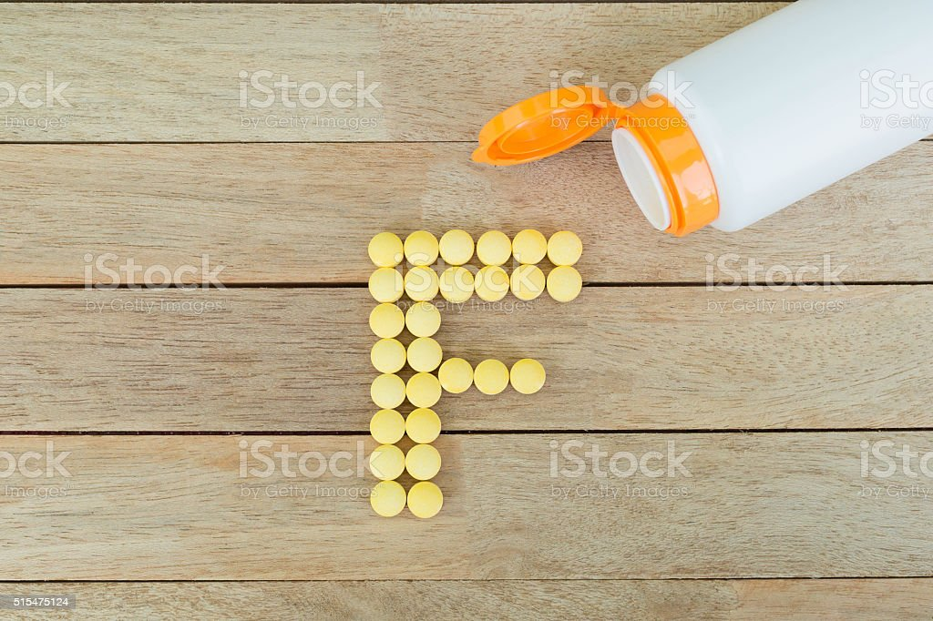 Yellow pills forming shape to F alphabet on wood background stock photo