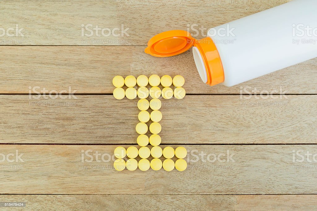 Yellow pills forming shape to I alphabet on wood background stock photo