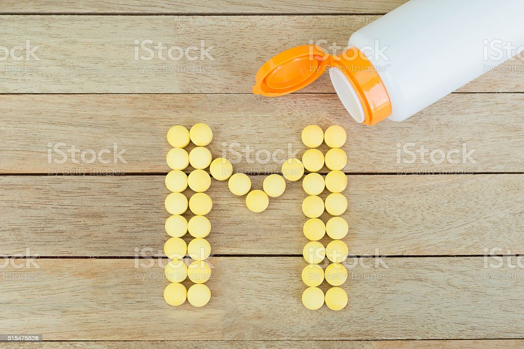 Yellow pills forming shape to M alphabet on wood background stock photo