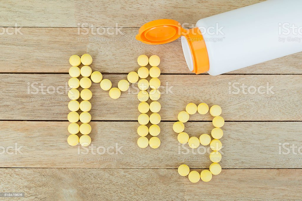 Yellow pills forming shape to Mg alphabet on wood background stock photo