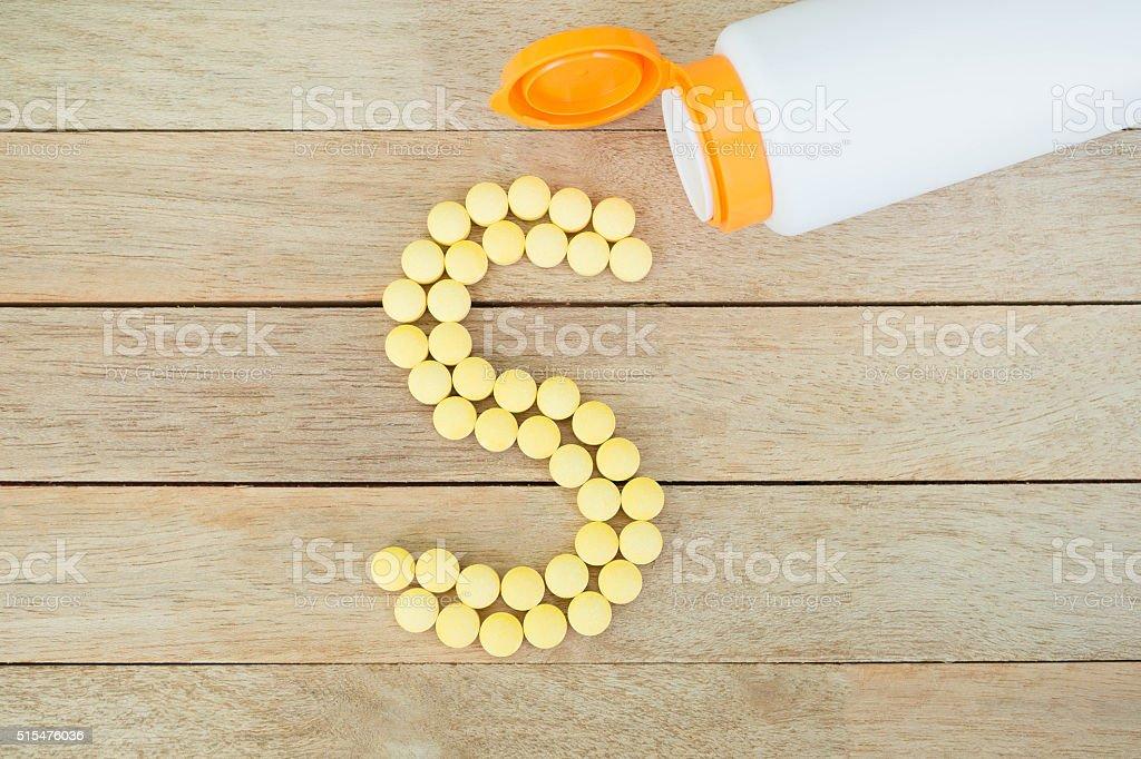 Yellow pills forming shape to S alphabet on wood background stock photo