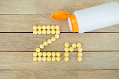 Yellow pills forming shape to Zn alphabet on wood background