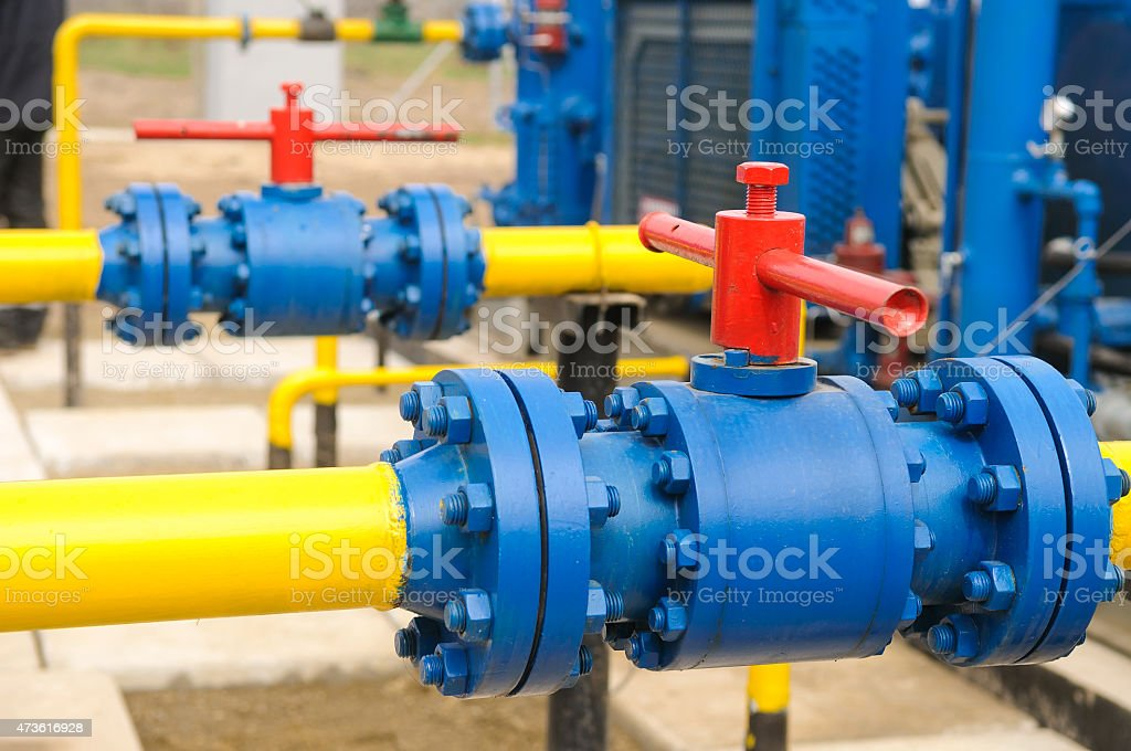 Yellow pipes with blue and red valves at a gas station stock photo