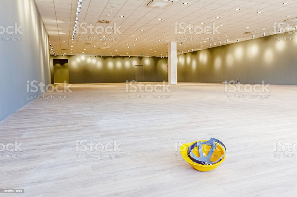 Yellow plastic safety helmet on the floor made of laminate. stock photo
