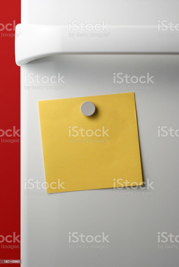 Yellow post it held on a fridge with one magnet stock photo