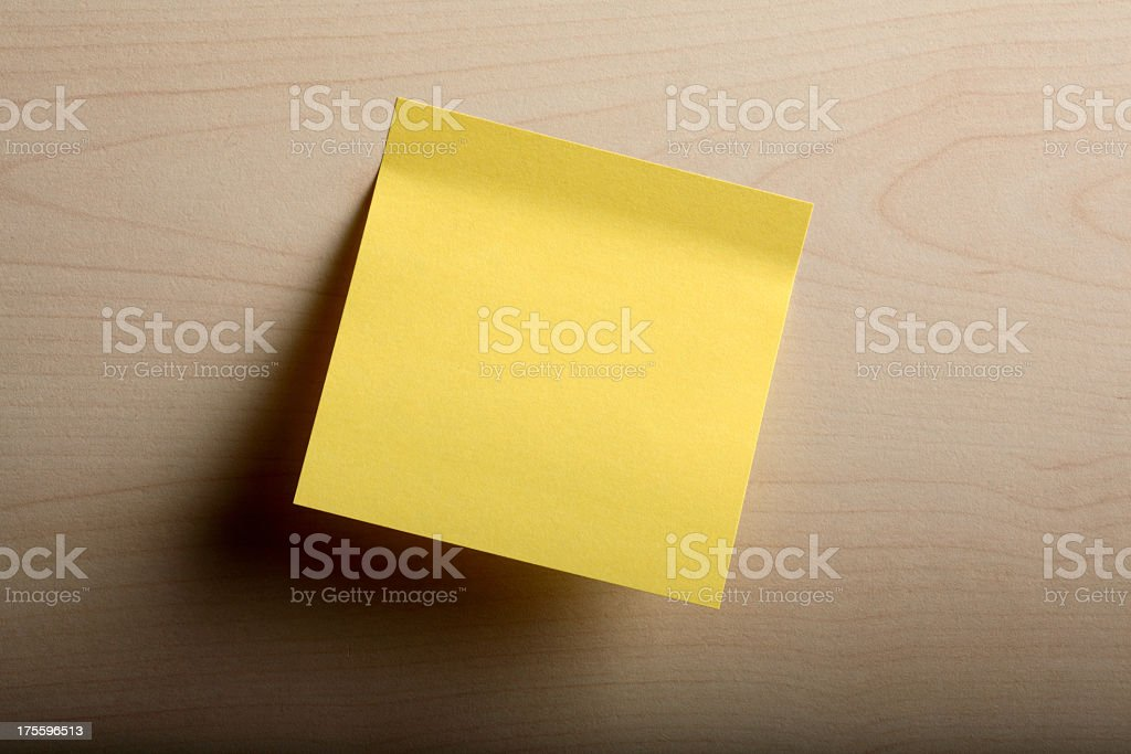 Yellow post it note on a light brown piece of wood stock photo
