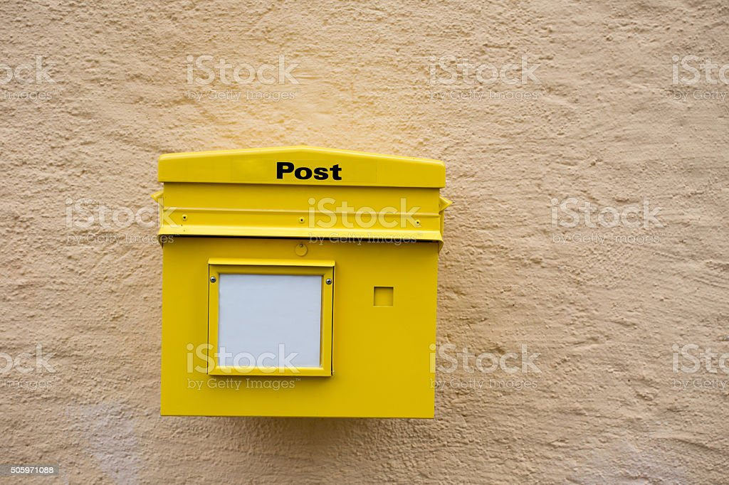Yellow postbox on the wall stock photo