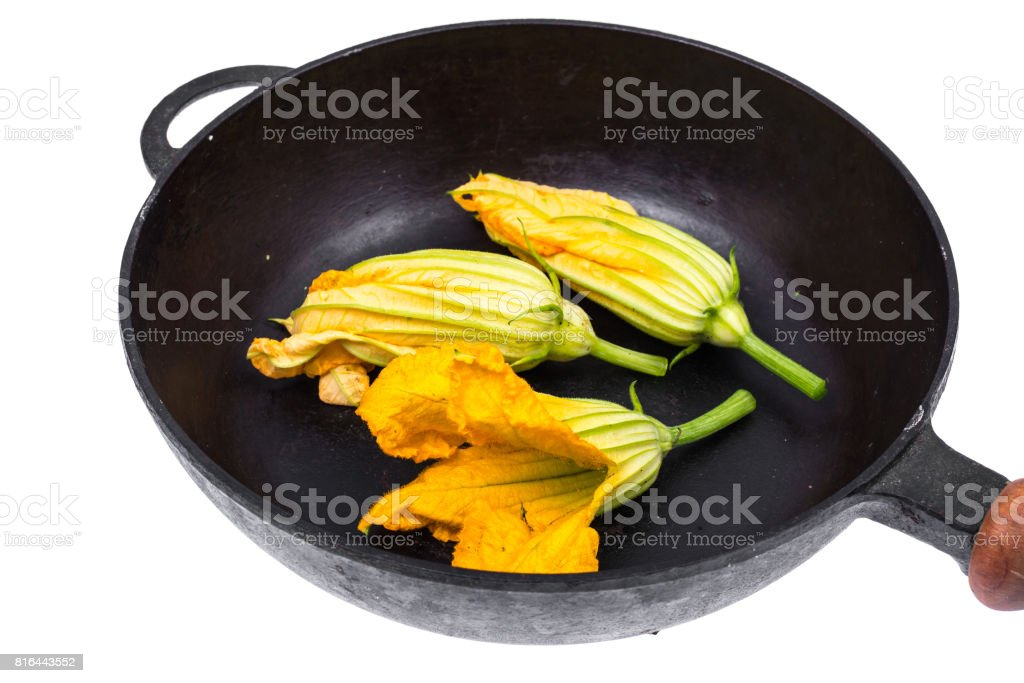 Yellow pumpkin flowers and zucchini in frying pan for cooking stock photo