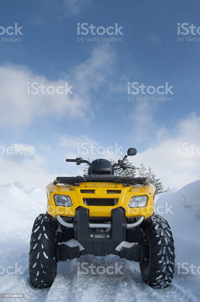 Yellow quadbike on snowy road royalty-free stock photo