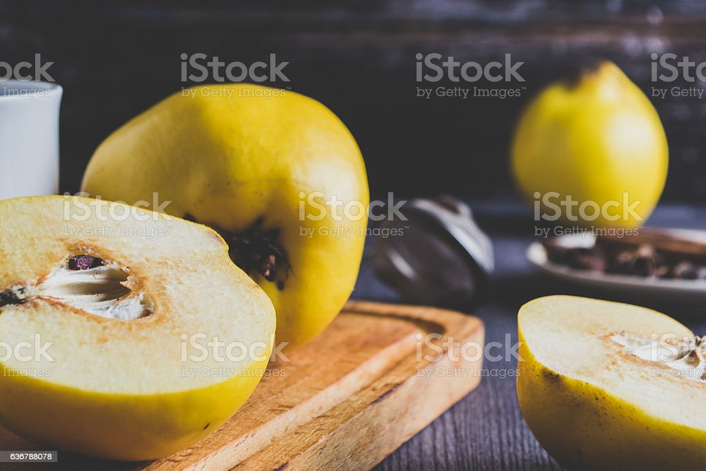 Yellow quince and tea on dark wooden background stock photo