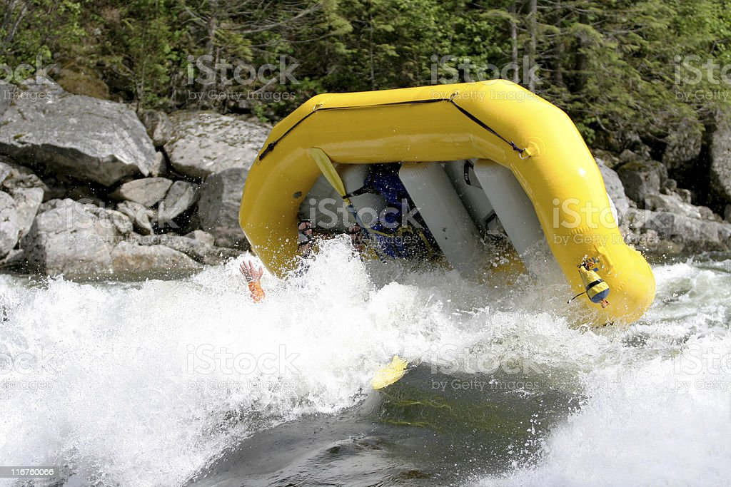 Yellow raft flipping over in a rapid. stock photo