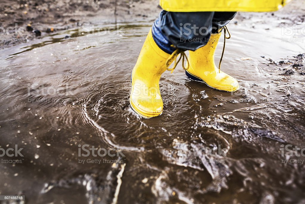 Yellow Rainboots In Puddle stock photo