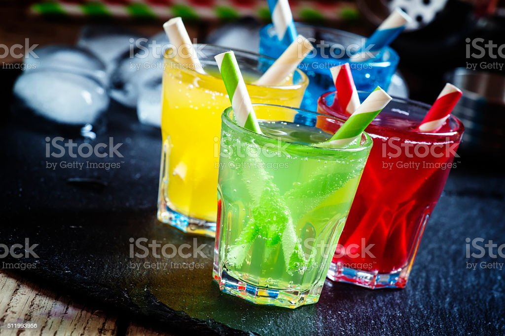 , yellow, red and green alcoholic cocktails with striped straws stock photo