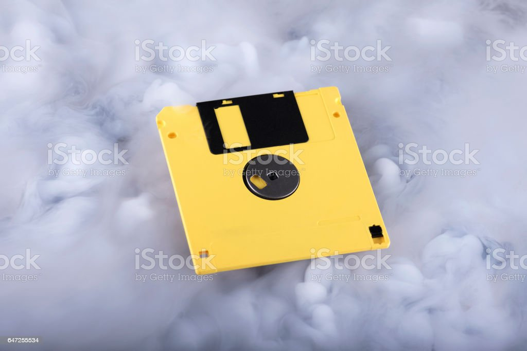 Yellow retro floppy disk in clouds. Information cloud conceptual image stock photo