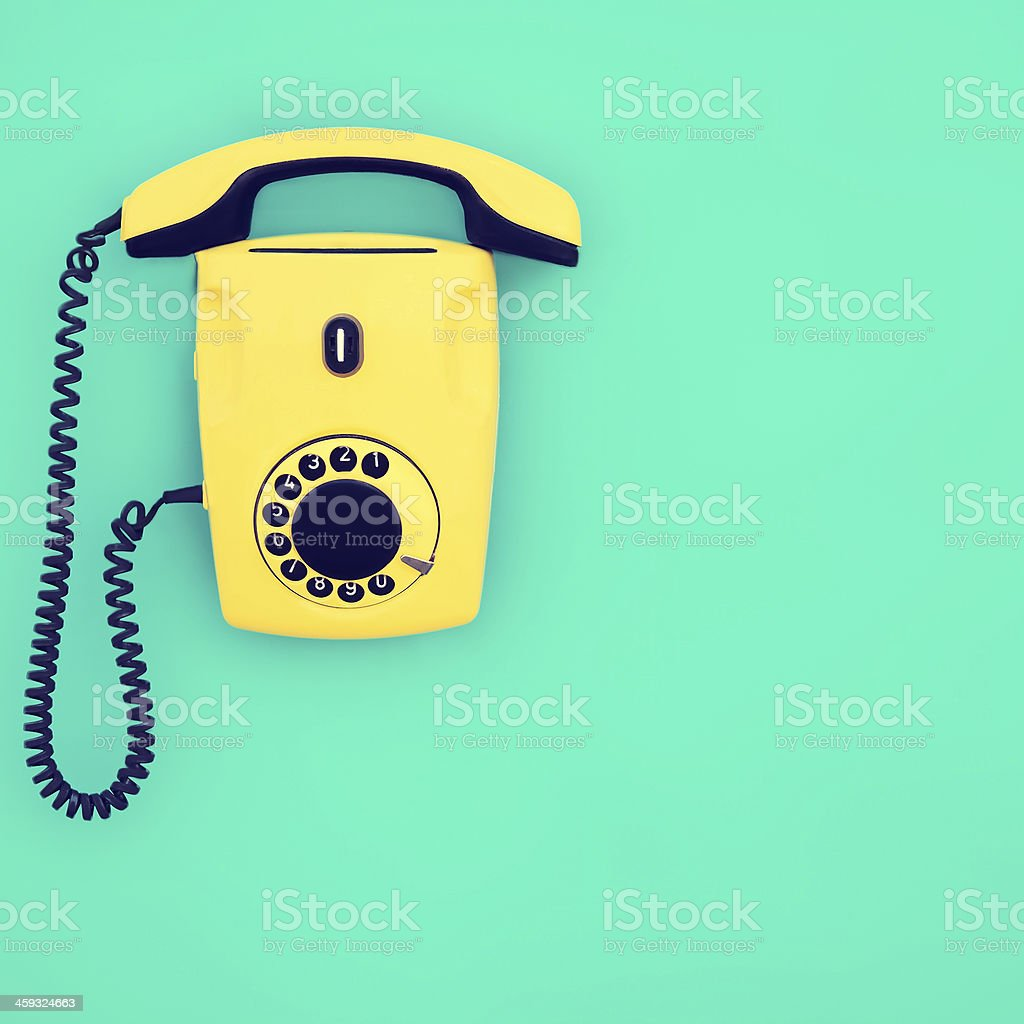 yellow retro telephone on a blue background stock photo