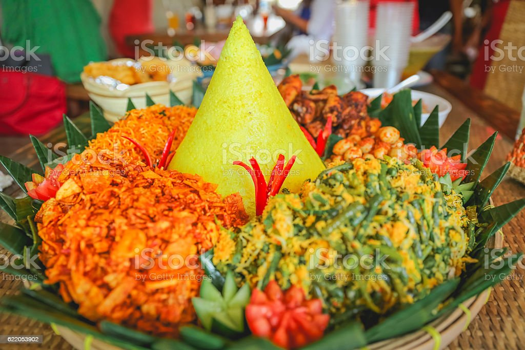 Yellow rice tumpeng with variation side dish stock photo