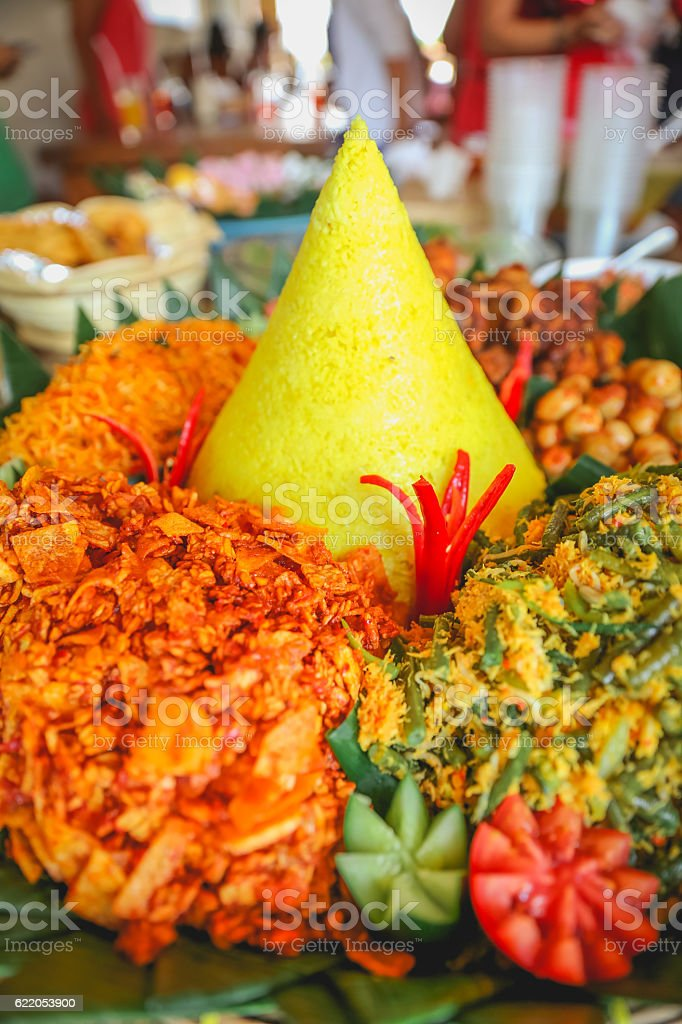 Yellow rice tumpeng with variety meat and vegetables stock photo