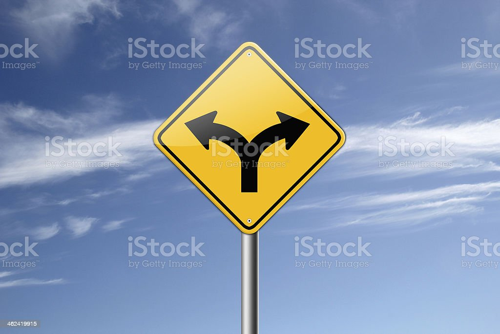 Yellow road sign showing forked road against a blue sky stock photo