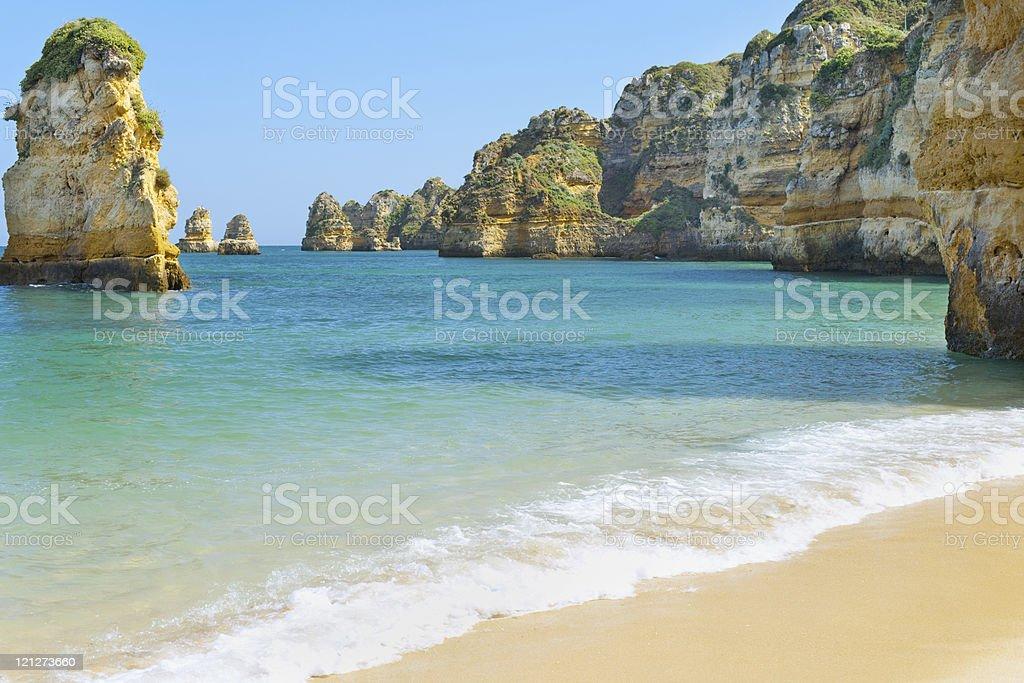 Yellow rocks and sandy beach stock photo