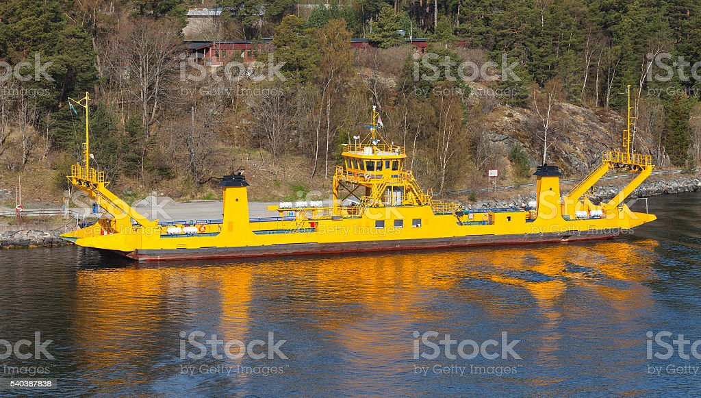 Yellow roro cargo ship goes near an island stock photo