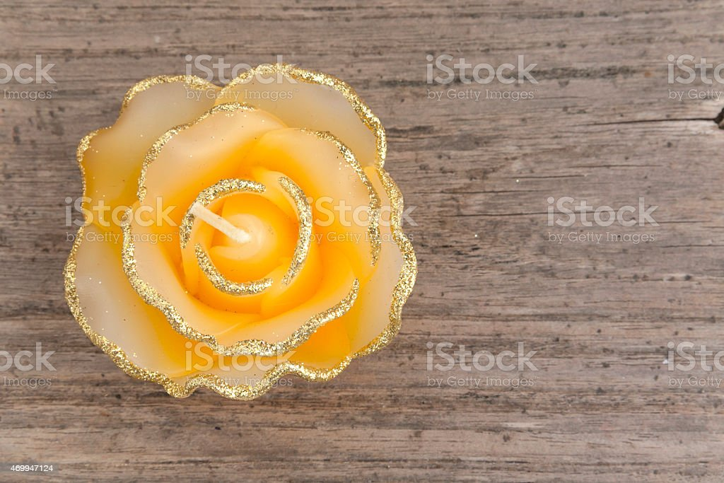 Yellow rose candle on wooden floor royalty-free stock photo