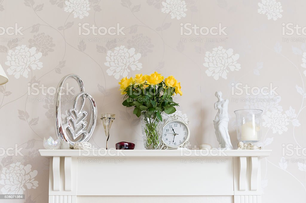Yellow roses, Venus de Milo and ornaments on mantlepiece stock photo