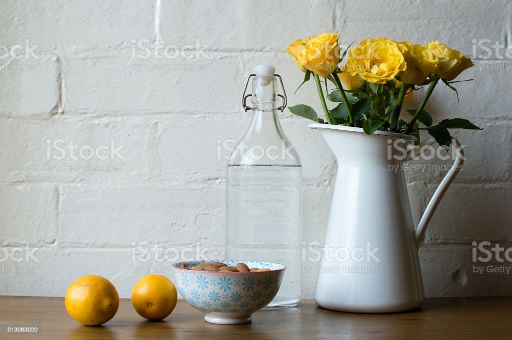 Yellow roses with water, almonds and lemons stock photo