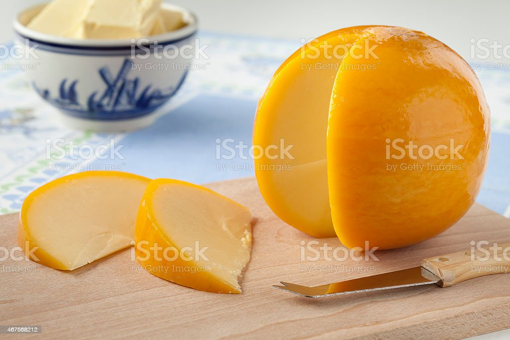 Yellow round Edam cheese and slices stock photo
