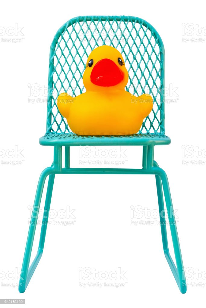 Yellow rubber duck sitting on a chair, sitting duck concept. stock photo