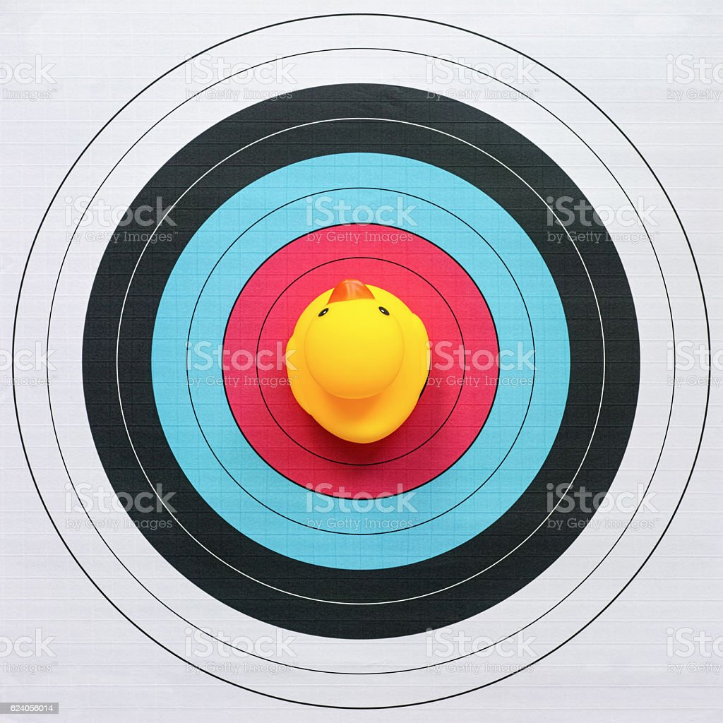 Yellow rubber duck sitting on the bulls-eye of a target. stock photo
