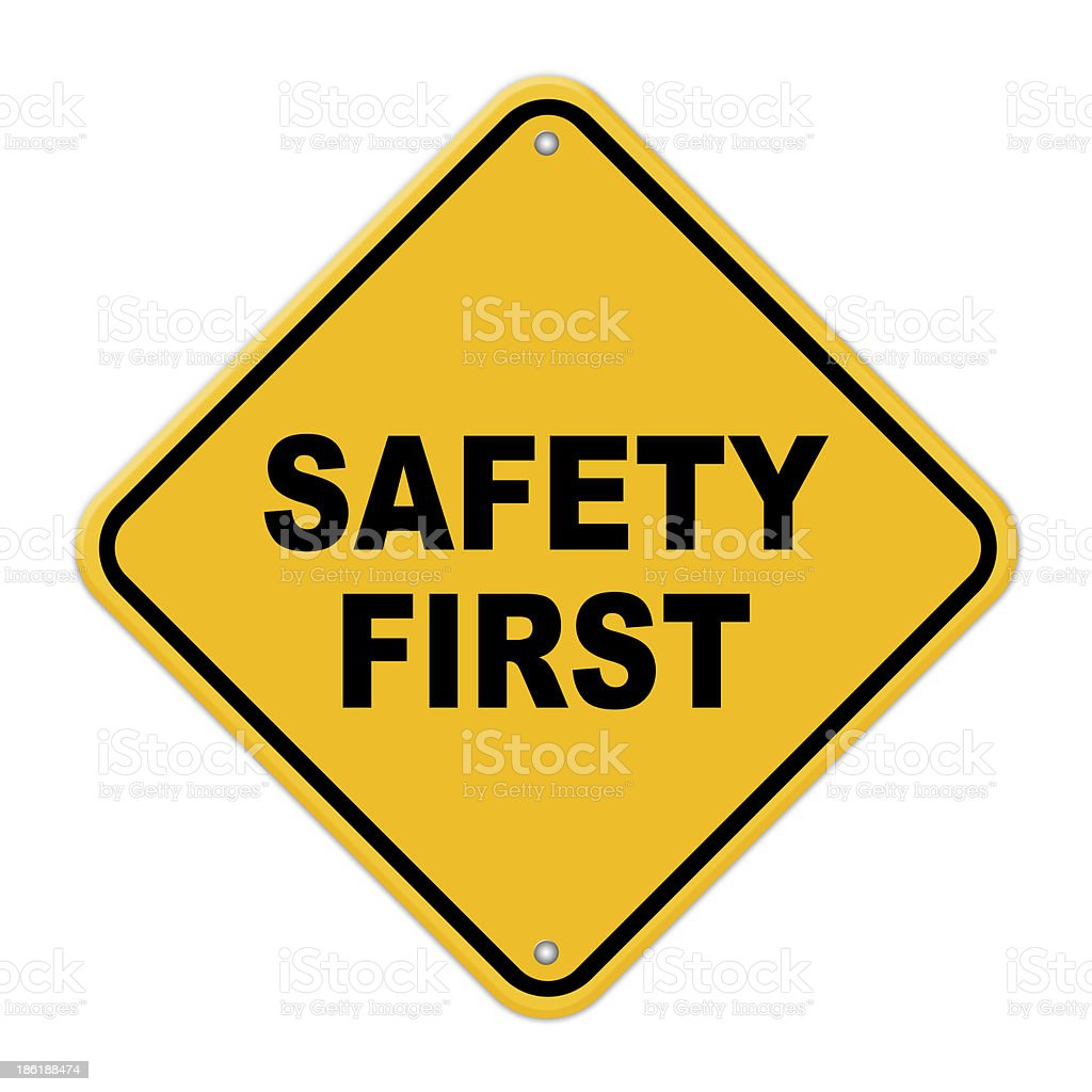 Yellow safety first road sign with rivets stock photo
