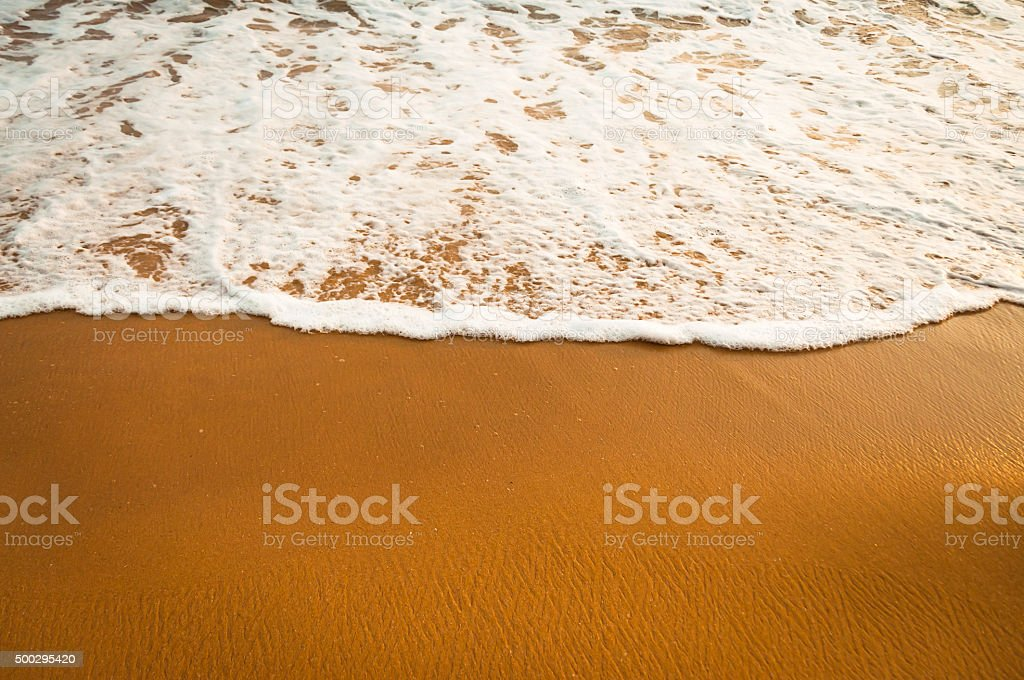 yellow sand and smooth ocean water with a bubbles stock photo