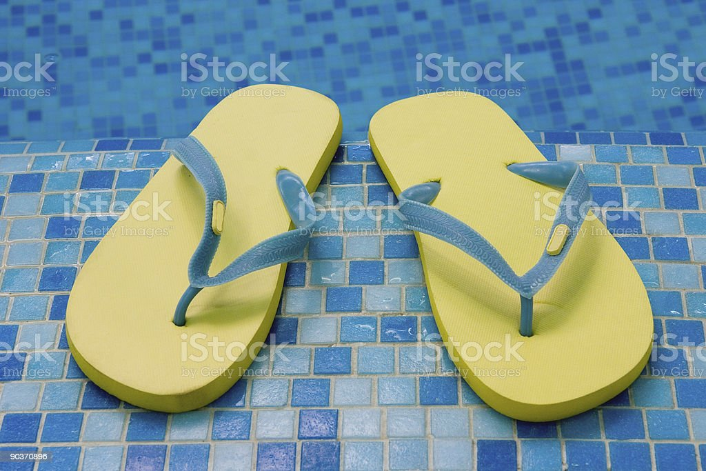 yellow sandals on the blue coast of pool royalty-free stock photo